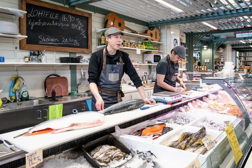 kauppias leikkaamassa kalaa